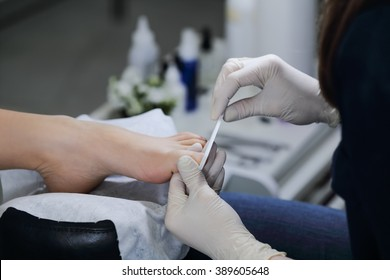 Close-up gash nail file toenails in salon. The service is professional pedicure in the spa salon.