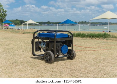Close-up gasoline powered portable generator on lakeshore sunny day Texas, US. Blurry high peak frame tent in background. Outdoor equipment standby, mobile backup for disaster recovery or construction
