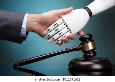 Close-up Of Gavel In Front Of Businessperson And Robot Shaking Hands