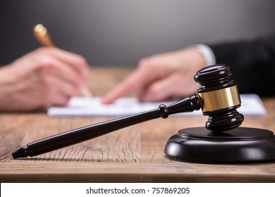 Close-up Of A Gavel In Front Of Judge Assisting Client To Sign Legal Document