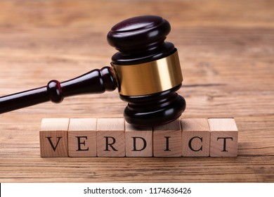 Close-up Of A Gavel Over Wooden Blocks With Text Verdict On Table