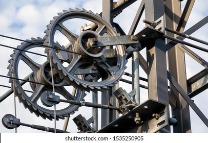 The close-up of gears of a wire tensioning device on a railway line. Stretching, tension pulleys with wires. Image of stretching of railroad wires fixed on the metalic lattice tower.