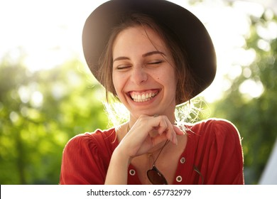 Close-up of gentle woman wearing big black summer hat and casual red shirt closing her eyes with pleasure smiling with joy being happy to spend nice warm summer day in park breathing fresh air