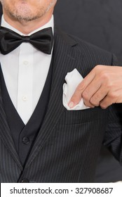 Close-up of a gentleman wearing Black Tie fixes his pocket square, vertical.