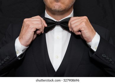 Close-up of a gentleman wearing Black Tie straightens his bowtie.