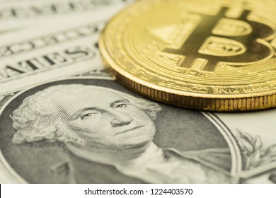 Closeup of George Washington's image on US Dollar banknote with golden Bitcoin cryptocurrency coin on top of it
