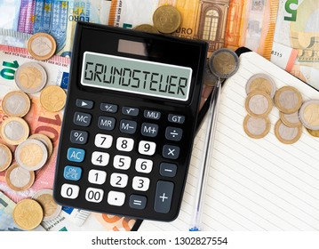 close-up of German word Grundsteuer (property tax or land tax) on display of pocket calculator with euro bills and coins in background