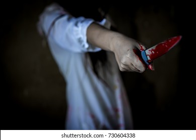 Closeup, Ghost woman or zombie hold knife for kill with blood violence in house of ruin, nightmare, horror of scary fear on hell is monster devil in halloween festival