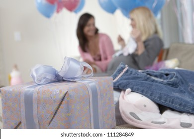 Close-up of gift and baby clothes with women in background at a baby shower
