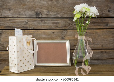 Close-up of gift bag, photo frame and flower vase on wooden surface