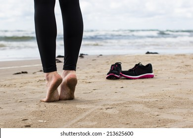 Close-up of gil's bare feet on wet sand. Running shoes and cold sea in the background.