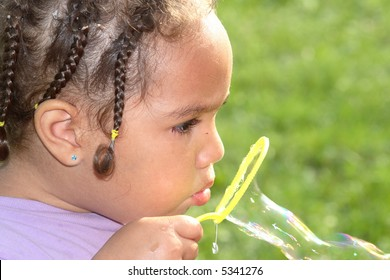 A close-up of a girl blowing bubbles with her yellow bubble wand