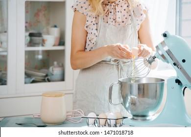 Nahaufnahme eines Mädchens, das ein Ei in die Schüssel eines Lebensmittelprozessors bricht und den Teig zubereitet, während es in der Küche steht