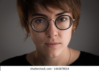 Close-up of girl with brown short hair and glasses looking at the camera with neutral expression