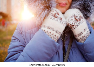 close-up girl in a down jacket and knitted woolen gloves basks in cold weather. winter fashion, hand care, fighting colds