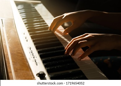 Close-up. The girl is engaged in online piano lessons. To the fingers that play the melody and the keys fall the sun's rays.