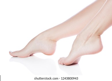 Close-up girl feet with clean smooth skin on heels. Isolated. White background. Body care female health concept