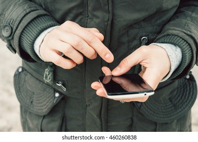 Close-up of a girl in a green jacket using a mobile phone with a touch screen outdoors