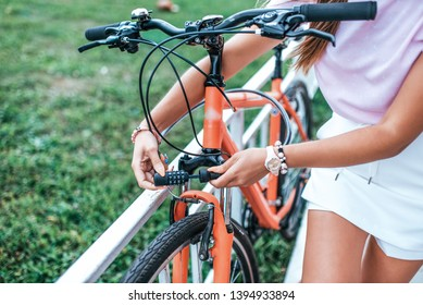 Close-up girl hand lock with digital cipher. Woman summer stands bicycle locking bicycle with cable. Picks password lock theft bicycle parking lot. Bicycle rentals Cycling weekend. Active lifestyle.
