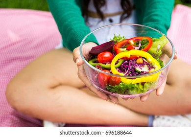 Close-up of girl hands holding fresh mixed colorful vegetable salad in glass bowl. vegetarian food. Healthy eating. woman with herb, lady diet, veggies people concept.