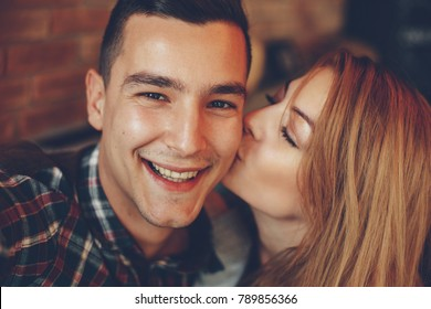 Closeup of girl kissing her boyfriend on the cheek