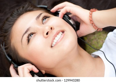 Closeup of a girl listening to the music with headphones