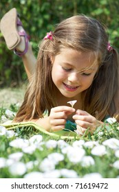 Close-up of girl lying on green grass and enjoying nice smell of tiny flower