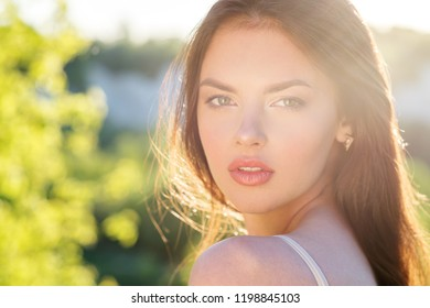 Closeup of girl posing outside in nature on a sunny day. Portrait of a young woman outdoors gree