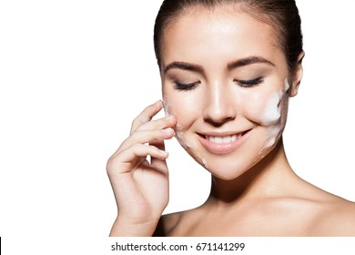 Close-up of a girl puts on the skin of the face foam for cleansing. Isolated on white background