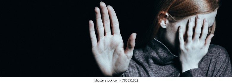 Close-up of girl with self-acceptance problem covering her face against black background with copy space