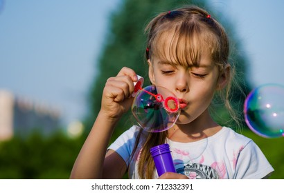 Close-up girl of six-years blowing bubble in a public park.