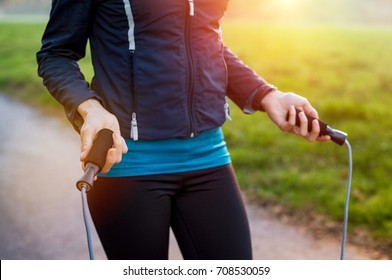 Closeup of girl skipping with a rope at park. Woman in jacket standing with a skipping rope in her hands at sunset. Young woman ready for skipping holding skipping rope in hands.