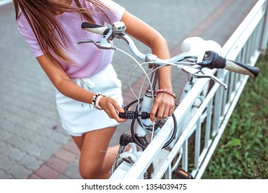 Close-up, a girl in summer city, puts lock on her bike, protection against theft, bicycle parking in the city. Closes the cipher, locking the lock with a password, metal cable, to protect bike.