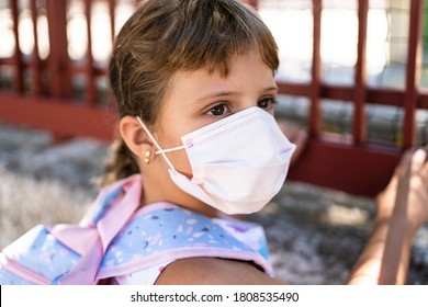 Close-up of a girl wearing a medical mask at the door of the school - Shutterstock ID 1808535490