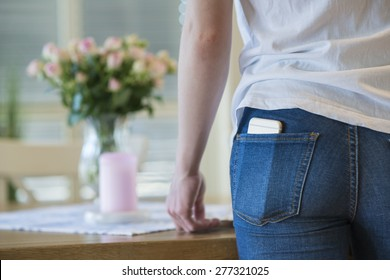 Close-up of a girl in white t-shirt and blue jeans with a cell or mobile phone in her back pocket.