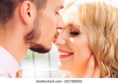 a close-up of a girlfriend closing her eyes and a guy who kisses her nose