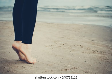 Close-up of girl's bare feet on cold wet sand. Toned image.