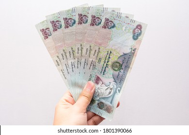 Closeup of a girl's hands holding UAE 500 dirhams currency notes, paper money against a light background