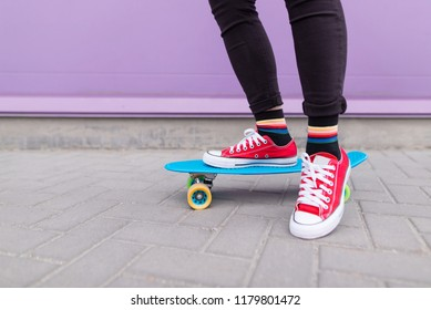 Close-up of a girl's legs in red sneakers standing on a purple skate on the background of a purple wall. Hipster girl on a skateboard. Street style.