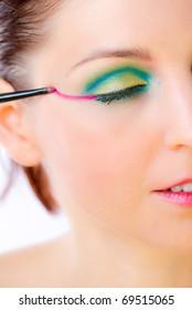 Closeup of a glamor fashion girl applying make-up