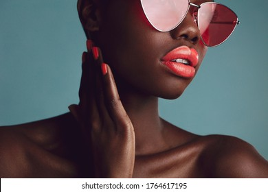 Close-up of a glamorous female model with artistic makeup wearing funky sunglasses. Attractive woman with red lipstick and nailpaint looking away on grey background.