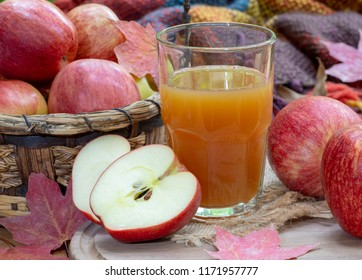 Closeup of a glass of apple cider and fresh red apples with autumn leaves and blanket in background