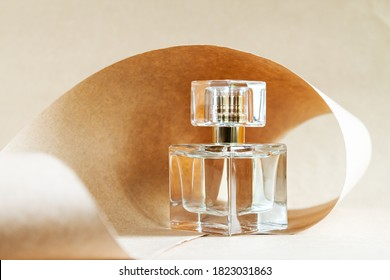 Closeup glass bottle of aromatic niche floral luxury perfume on abstract background of craft paper. Cosmetics, products for personal care and concept. Minimalistic packing, branding.