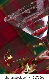 Closeup of glass of Candy Cane Martini and Christmas ornaments
