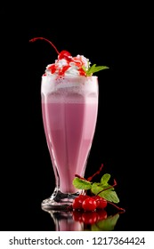 Closeup glass of cherry milk shake decorated with mint and berries isolated at black background.