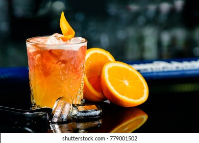 Closeup glass of classic alcohol cocktail godfather on the bar with slice of orange and ice cubes