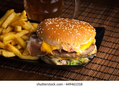 Closeup of a glass of cold beer, french fries and cheese burgher served on wooden board