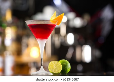 Closeup glass of cosmopolitan cocktail decorated with orange at bar background.