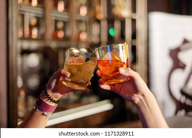 close-up glass  of friends clinking glasses of whiskey