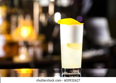 Closeup glass of gin fizz cocktail with lemon and whip eggwhite at bar cpunter background.